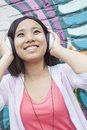 Young smiling woman holding her headphones while enjoying listening to music in front of wall with graffiti women Stock Images
