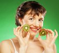 Young smiling woman holding kiwi over green background Royalty Free Stock Image