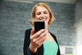 Young smiling woman holding smartphone in office Royalty Free Stock Photos