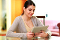 Young smiling woman holding tablet computer at home Stock Image