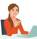 Young smiling woman with a laptop at a desk holding a coffee cup