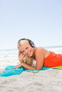Young smiling woman lying on her beach towel while listening to Royalty Free Stock Image