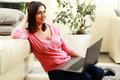Young smiling woman sitting on the floor and using laptop at home Stock Photo