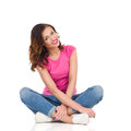 Young smiling woman sitting with legs crossed in pink shirt and jeans on a floor full length studio shot isolated on white Royalty Free Stock Photography