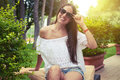 Young smiling woman sitting in sunny summer garden Royalty Free Stock Photo
