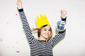 Young smiling woman on white background celebrating party, wearing stripped dress and yellow paper crown, happy dynamic