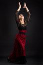 Young spanish woman dancing flamenco on black dancer in and red dress Royalty Free Stock Images