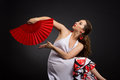 Young spanish woman dancing flamenco on black dancer in white and red dress with red fan over background Stock Photos
