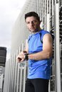 Young sport man checking time on chrono timer runners watch holding water bottle after training session Royalty Free Stock Photo