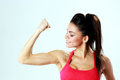 Young sport woman looking at her biceps on gray bakground Royalty Free Stock Photo