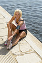 Young sport woman stretch legs water pier Stock Photography