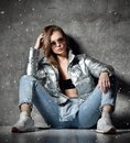 Young sport woman after workout exercise sitting under snow in silver thin down puffer jacket blue jeans Royalty Free Stock Photo