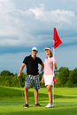 Young sportive couple playing golf on a course Stock Image
