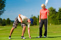 Young sportive couple playing golf on a course he takes the ball from the hole Royalty Free Stock Photo