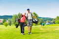 Young sportive couple playing golf on a course they walking to the next hole Stock Photo