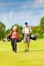 Young sportive couple playing golf on a course they walking to the next hole Royalty Free Stock Photos