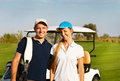 Young sportive couple playing golf on a golf course standing near the golfcar Stock Photos