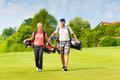 Young sportive couple playing golf on a golf course they walking to the next hole Stock Image