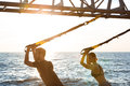 Young sportive people training with trx near sea in the morning. Royalty Free Stock Photo