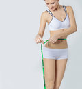 Young sports a beautiful slim woman measuring perfect shape nice hips, the concept of a healthy lifestyle on a white background Royalty Free Stock Photo