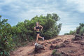 Young sportswoman cross country running on dirty rocky footpath in mountains in summer. Fit girl jogging outdoors in Royalty Free Stock Photo
