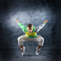 A young and sporty caucasian man in attractive clothes doing a modern dance pose the image is taken on a grunge blue background Stock Images