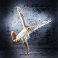 A young and sporty caucasian man in attractive clothes doing a modern dance pose the image is taken on a grunge blue background Royalty Free Stock Photos