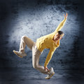 A young and sporty caucasian man in attractive clothes doing a modern dance pose the image is taken on a grunge blue background Royalty Free Stock Photography