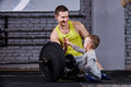 Young sporty father and little cute son sitting near barbell against brick wall in the cross fit gym. Royalty Free Stock Photo