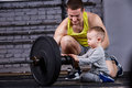 Young sporty father showing dumbbells for his little son and smiling against brick wall in the cross fit gym. Royalty Free Stock Photo