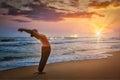 Young sporty fit man doing yoga sun salutation surya namaskar pose hasta uttanasana on tropical beach on sunset with lens flare Stock Photography