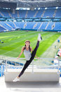 Young sporty girl jumped high and spread her legs in different directions on the background of a football stadium. Woman in sports Royalty Free Stock Photo