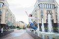 Young sporty girl jumping for joy at the fountain in the residential complex. Female in flight with his hands up Royalty Free Stock Photo