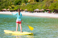 Young sporty girl on vacation tropical beach paddling stand up board Stock Image