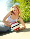 Young sporty woman with ball on the beach green background Royalty Free Stock Image