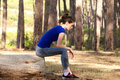Young sporty woman resting on log outside Royalty Free Stock Photo