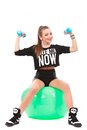 Young sporty woman sitting on fitball with dumbbells on white ba background Royalty Free Stock Photo