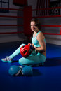 Young sporty woman sitting near lying boxing gloves and helmet Royalty Free Stock Photo