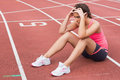 Young sporty woman sitting on the running track Royalty Free Stock Photos
