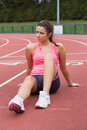 Young sporty woman sitting on the running track Royalty Free Stock Image