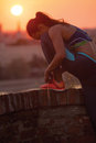 Young sporty woman tying shoelaces in the sunset Stock Photo