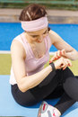 Young sporty woman using fitness wristband watch her slim girl with smart device on workout training Stock Photos