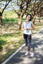 Young sporty woman using smartphone with headphone in park