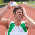 Young sprinter spraying water on his head Stock Photos