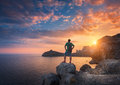Young standing man with backpack on the stone at sunset Royalty Free Stock Photo