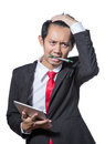 Young Stressed business man holding tablet and bite pen Royalty Free Stock Photo