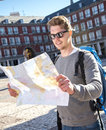 Young student backpacker tourist looking city map in holidays travel attractive europe outdoors enjoying destination tourism Royalty Free Stock Image