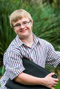 Young student with down syndrome holding files outdoors. Royalty Free Stock Photo