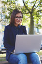 Young student girl in glasses sitting on the campus bench while use laptop gadget during her class break portrait of attractive Stock Image