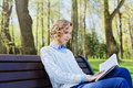 Young student girl in shirt sitting with a book in her hand in a green park, science and education, reading Royalty Free Stock Photo